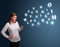 Young woman typing on smartphone with high tech 3d letters commi Royalty Free Stock Photos