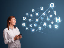 Young woman typing on smartphone with high tech 3d letters commi Stock Photo