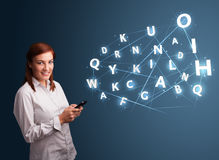 Young woman typing on smartphone with high tech 3d letters commi. Beautiful young woman typing on smartphone with high tech 3d letters comming out Stock Photography