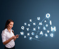 Young woman typing on smartphone with high tech 3d letters commi Royalty Free Stock Photography