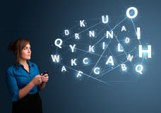 Young woman typing on smartphone with high tech 3d letters commi Stock Photos