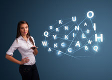 Young woman typing on smartphone with high tech 3d letters commi Royalty Free Stock Photo