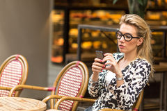 Young woman typing on a smartphone sitting in outdoors cafe. Stock Images
