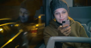 Young woman typing sms during bus ride stock video footage
