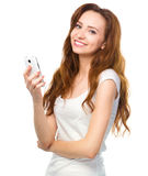 Young woman is typing sms message on her phone Stock Image