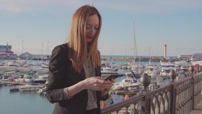 Businesswoman is sending messages by mobile standing on terrace with port view. Young woman is typing sms in mobile phone in sunny day. She is standing on stock footage