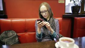 Young woman typing to her boyfriend on smartphone in cafe on the couch. Love and relationships. She using app on phone. Young woman typing to her boyfriend on stock footage
