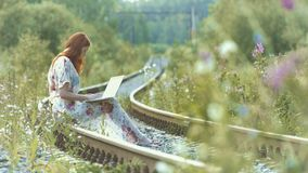 Young woman typing on a white laptop. 2 Shots. Slow motion. 1. A beautiful red-haired girl sits on the rail with a laptop on her lap and presses the keys stock video
