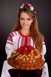 Young woman in ukrainian clothes and round loaf Royalty Free Stock Image