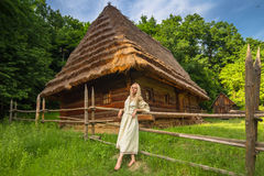 Young woman in ukrainian national costume near old house. Young woman in ukrainian national costume near old wooden house (wide angle lense Stock Image