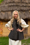 Young woman in ukrainian national costume - smiling. Young woman in ukrainian national costume near old historic house Stock Photography