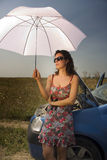 Young woman with umbrella. Sitting on a broken car Royalty Free Stock Image