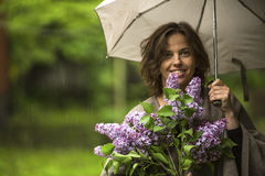 Young woman with umbrella and branch of lilac, outdoors in the rain. Royalty Free Stock Photography