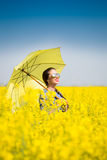 Young woman with an umbrella in canola field Stock Photo