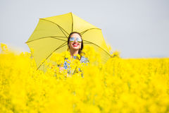 Young woman with an umbrella in canola field Stock Image