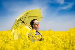 Young woman with an umbrella in canola field Stock Photography