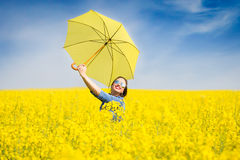 Young woman with an umbrella in canola field Stock Images