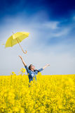 Young woman with an umbrella in canola field Royalty Free Stock Photography