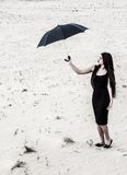 Young woman with an umbrella in a desert Royalty Free Stock Photo