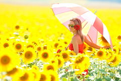 Young woman with umbrella on field in summer Royalty Free Stock Images