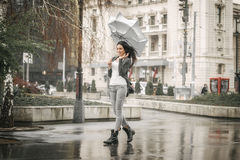 Young woman with umbrella in hand fighting with strong wind Stock Photos