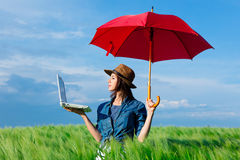 Young woman with umbrella and laptop. Portrait of young beautiful woman with red umbrella and laptop in the field Royalty Free Stock Photo