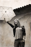 Young woman with umbrella  near the old house Stock Image