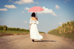 Young woman with umbrella. Photo of the beautiful young woman with umbrella walking on the road Royalty Free Stock Image