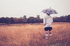 Young woman with umbrella standing in field Royalty Free Stock Photography