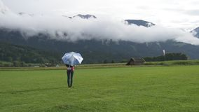 A young woman with umbrella standing and walking on grass. A young woman with umbrella standing on green field, then walking towards mountains topped with clouds stock footage