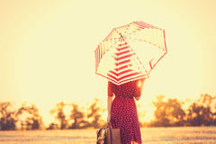 Young woman with umbrella and suitcase Stock Images