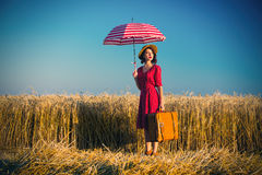 Young woman with umbrella and suitcase Royalty Free Stock Image
