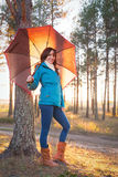 Young woman with umbrella in sunset lights in forest. Young woman with umbrella in sunset lights in the forest royalty free stock photo