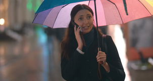 Young woman with umbrella talking on the phone. Young happy woman having exciting phone talk holding colorful umbrella in rainy evening in the city stock footage