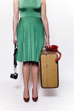 Young woman with umbrella traveling. A well dressed young woman with a bright red umbrella, suite case and camera Royalty Free Stock Image