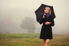 Young fashion woman with umbrella walking in a fog outdoor Royalty Free Stock Photography