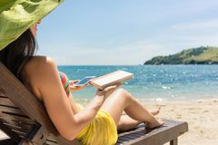 Young woman undecided between reading a book and spending time o. N internet while sitting on the beach during summer vacation in Indonesia Royalty Free Stock Photos