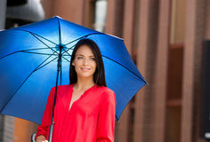 Young woman under a blue umbrella Stock Images