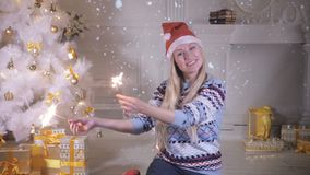 A happy woman with sparklers near a Christmas tree. stock video