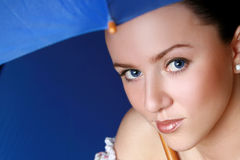 Young woman under dark-blue umbrella Royalty Free Stock Photo