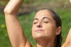 Young woman under the drops. A woman under the shower Royalty Free Stock Photography