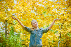 Young woman under the shower of autmn leaves. Young woman with autumn leaves falling on it and fall yellow maple garden background Stock Photo