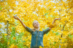 Young woman under the shower of autmn leaves. Young woman with autumn leaves falling on it and fall yellow maple garden background Stock Images