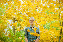 Young woman under the shower of autmn leaves. Young woman with autumn leaves falling on it and fall yellow maple garden background Royalty Free Stock Photo