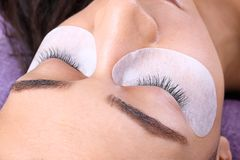 Young woman undergoing eyelash extensions procedure,. Closeup royalty free stock image
