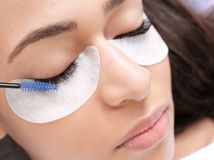 Young woman undergoing eyelash extensions procedure,. Closeup Stock Images
