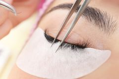 Young woman undergoing eyelash extensions procedure,. Closeup Stock Photo
