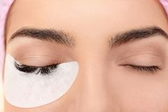 Young woman undergoing eyelash extensions procedure. Closeup Stock Photo