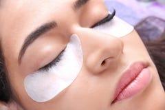 Young woman undergoing eyelash extensions procedure. Closeup stock images