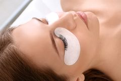 Young woman undergoing eyelash extensions procedure. Closeup royalty free stock images